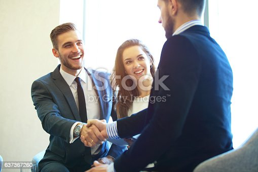 656005826istockphoto Business people shaking hands, finishing up a meeting. 637367260