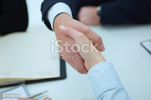 656005826istockphoto Business people shaking hands, finishing up a meeting. 872249316