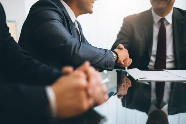hombres de negocios estrechándose las manos, acabado de una reunión - abogado fotografías e imágenes de stock