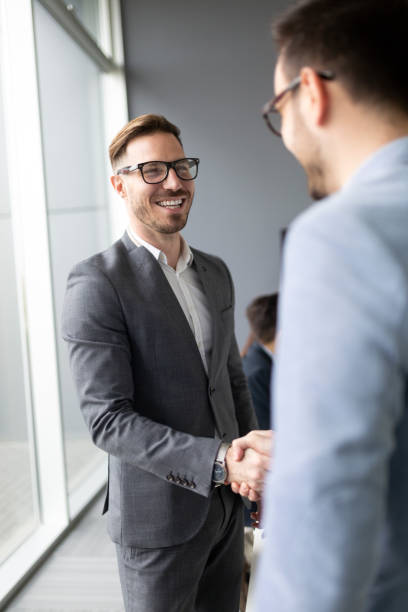 Business people shaking hands, finishing up meeting Business people shaking hands, finishing up successful meeting dealing cards stock pictures, royalty-free photos & images