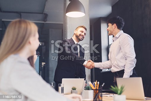 Business people shaking hands, finishing up meeting in board room