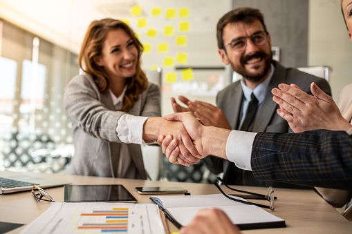 656005826 istock photo Business people shaking hands, finishing up meeting 1251201182