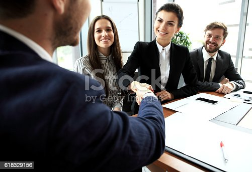656005826istockphoto Business people shaking hands, finishing up meeting 618329156