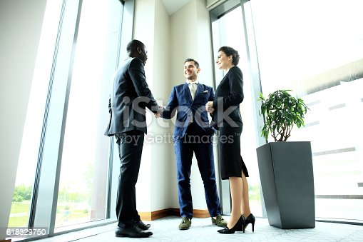 656005826istockphoto Business people shaking hands, finishing up meeting 618329750