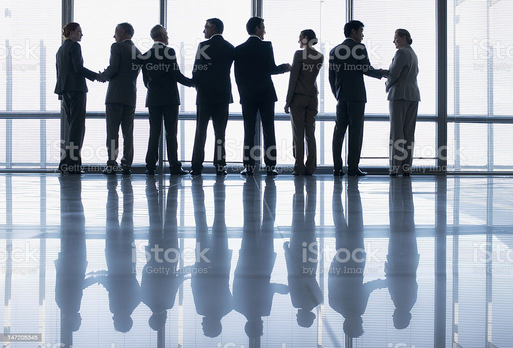 Business people shaking hands in a row at lobby window stock photo