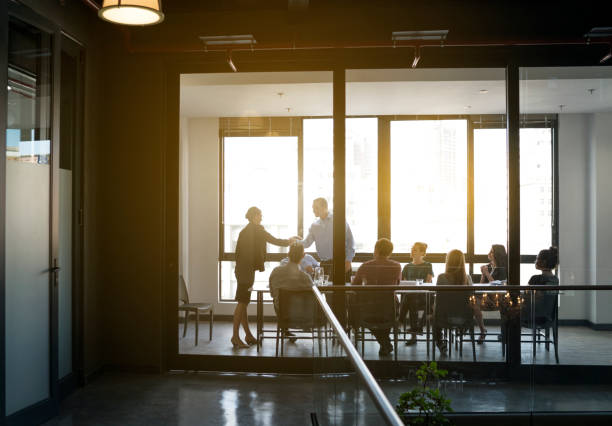 Business people shaking hands in board room Businesswoman shaking hands with male professional in board room. Executives are seen through glass walls at brightly lit office. All are in meeting. board room stock pictures, royalty-free photos & images