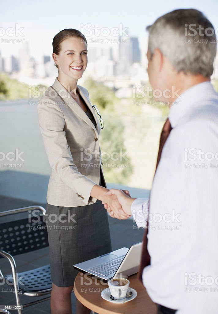 Business people shaking hands in cafe royalty-free stock photo
