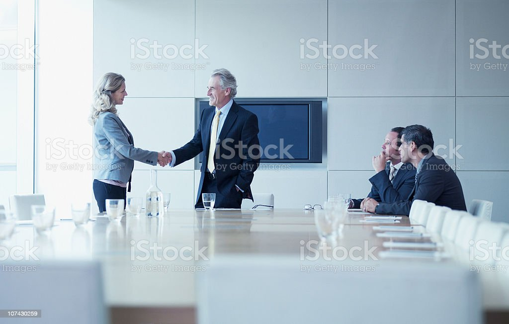 Business people shaking hands in conference room stock photo