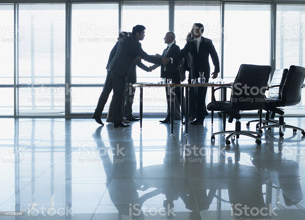 Business people shaking hands in conference room royalty-free stock photo