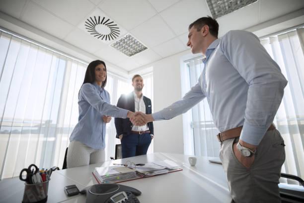 Hombres de negocios estrechándose las manos en la sala de conferencias - foto de stock