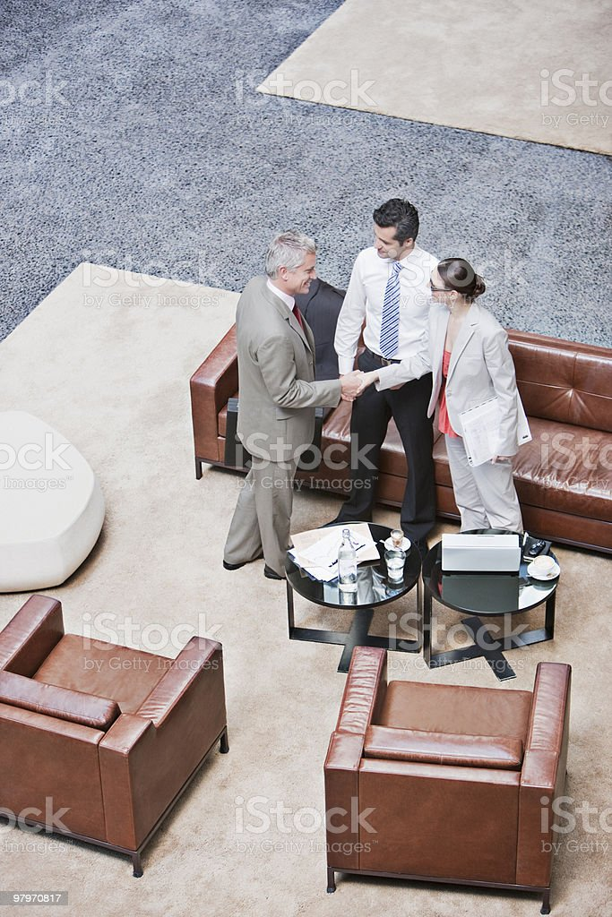 Business people shaking hands in lobby royalty-free stock photo