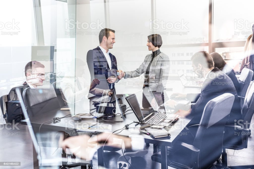 Business people shaking hands in moder corporate office. stock photo