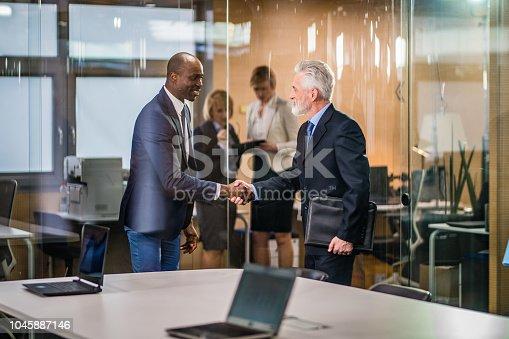 Businessmen shaking hands in conference room.