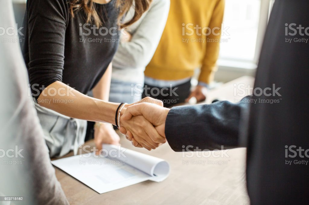 Business people shaking hands in office Cropped shot of businessman greeting a young professional around the table in office. Close up of business people shaking hands in office. Adult Stock Photo