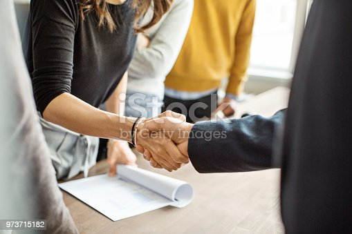 Cropped shot of businessman greeting a young professional around the table in office. Close up of business people shaking hands in office.