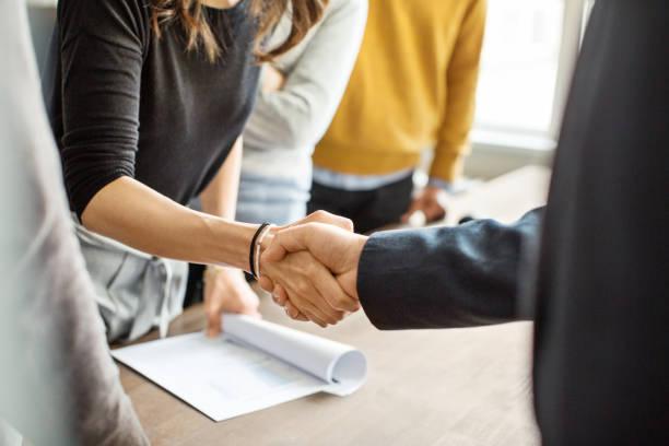 gens d'affaires se serrant la main dans le bureau - se saluer photos et images de collection