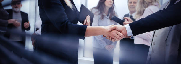 Geschäftsleute schütteln Hände, während sie in der Nähe eines Bürofensters stehen – Foto