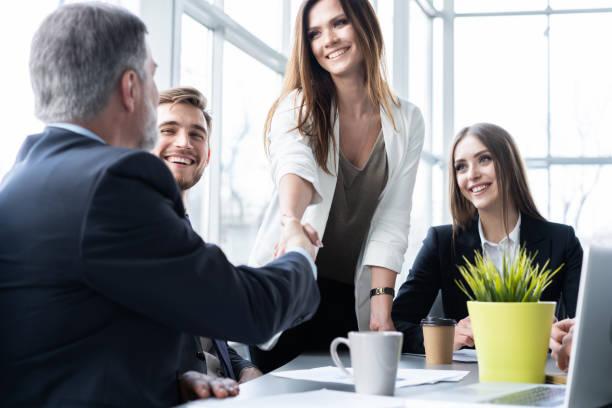 Geschäftsleute schütteln sich während der Arbeit im Kreativbüro die Hände – Foto