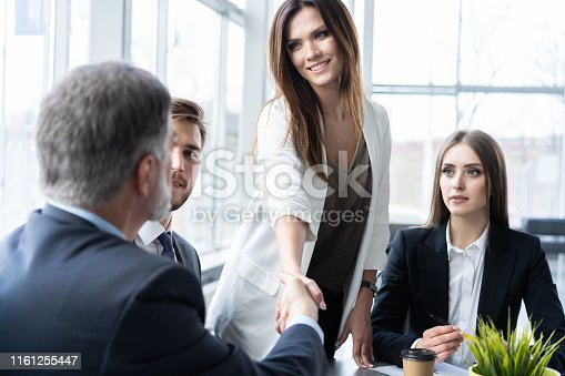 951514270 istock photo Business people shaking hands while working in the creative office 1161255447