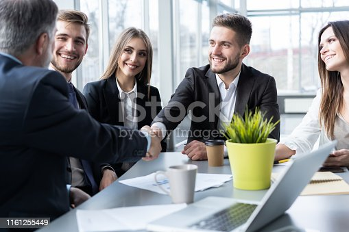 951514270 istock photo Business people shaking hands while working in the creative office 1161255449