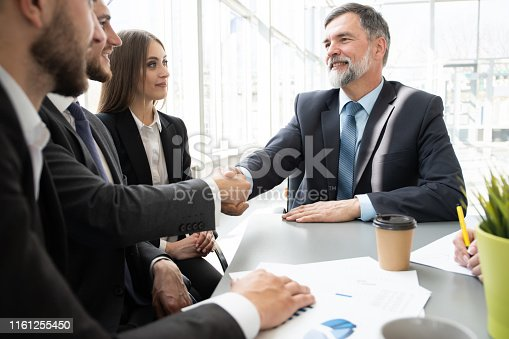 951514270 istock photo Business people shaking hands while working in the creative office 1161255450