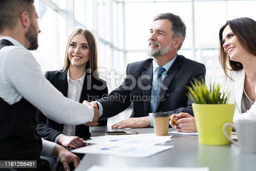 951514270 istock photo Business people shaking hands while working in the creative office 1161255451