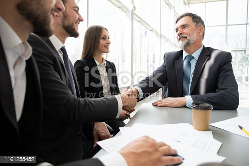 951514270 istock photo Business people shaking hands while working in the creative office 1161255452