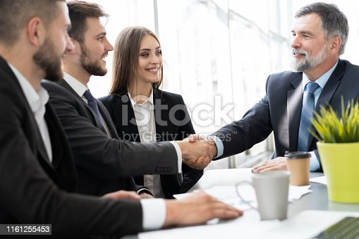 951514270 istock photo Business people shaking hands while working in the creative office 1161255453
