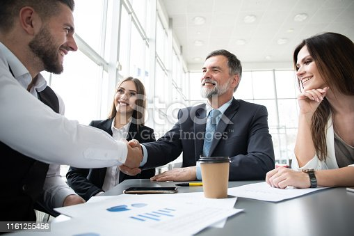 951514270 istock photo Business people shaking hands while working in the creative office 1161255456
