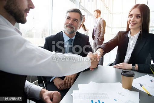 951514270 istock photo Business people shaking hands while working in the creative office 1161255457