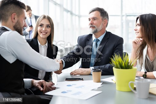 951514270 istock photo Business people shaking hands while working in the creative office 1161255462