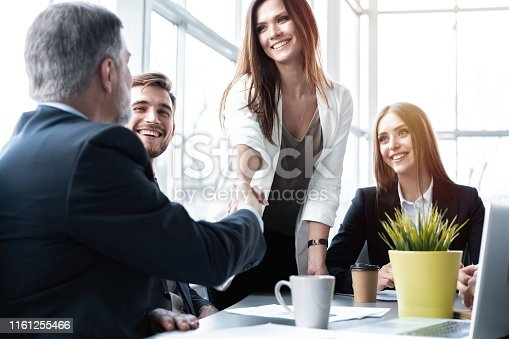 951514270 istock photo Business people shaking hands while working in the creative office 1161255466