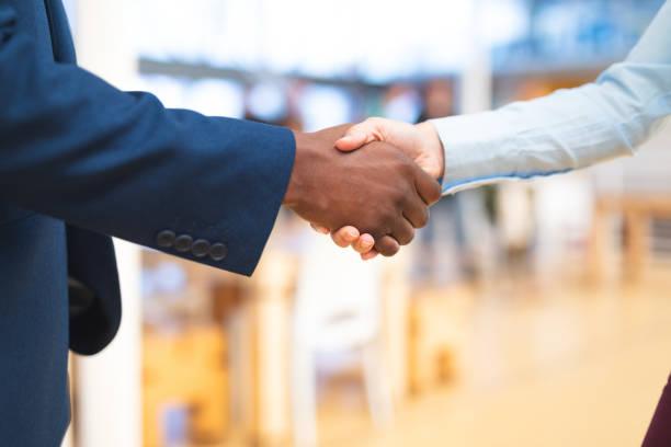gens d'affaires se serrant la main les uns avec les autres dans le couloir au bureau - se saluer photos et images de collection
