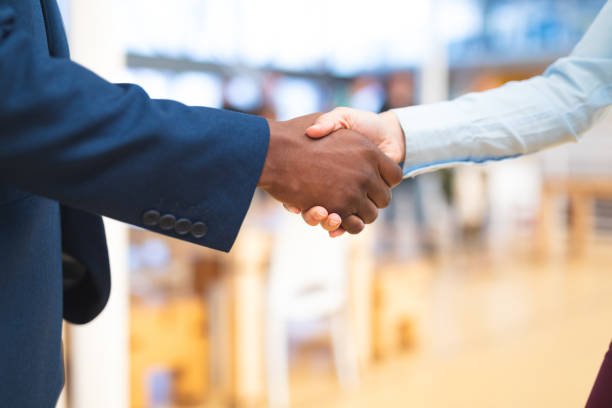 Business people shaking hands with each other in corridor at office stock photo