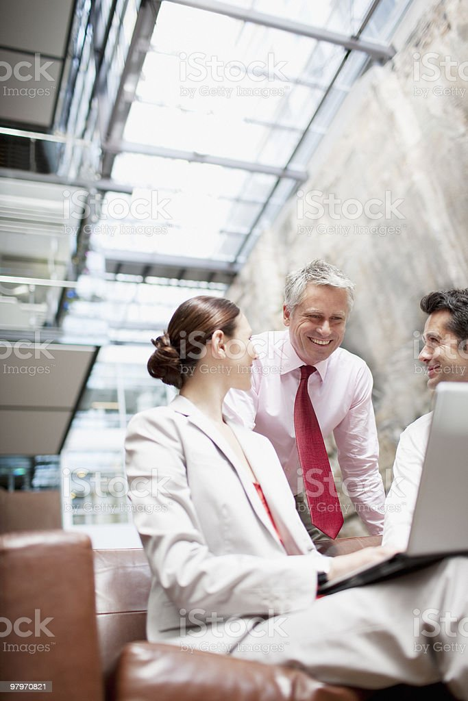 Business people sharing computer on lobby sofa royalty-free stock photo