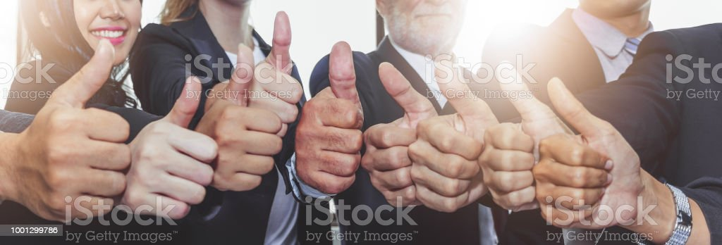 Business people showing thumbs up for teamwork and together concept Business people showing thumbs up for teamwork and together concept Achievement Stock Photo