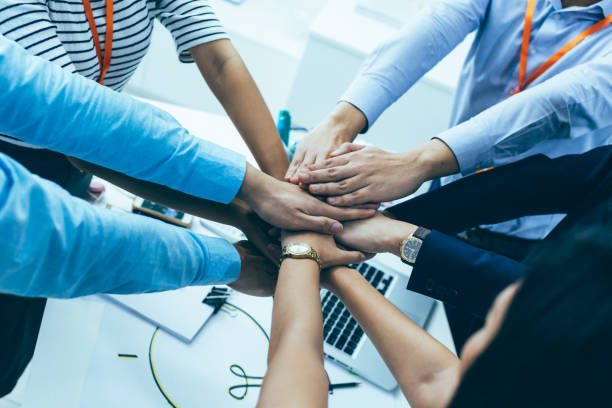 Business people showing unity and collaboration gesture stock photo