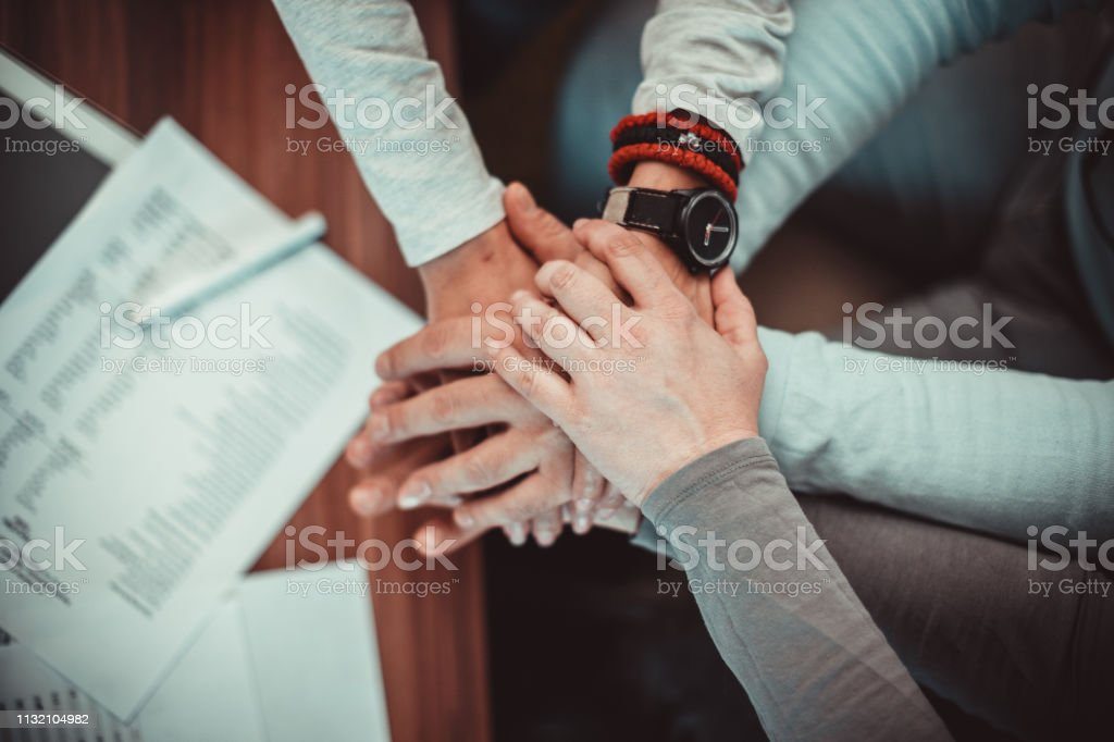 Business people showing unity - holding hands stock photo