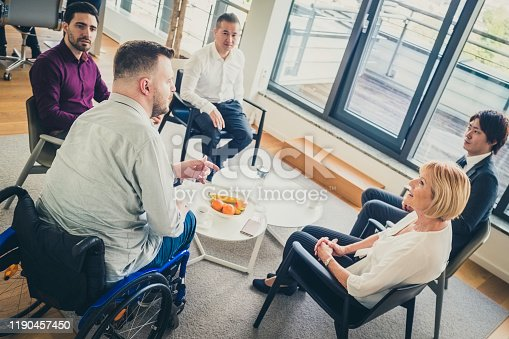 A group of business people sitting around a coffee table in an office and talking.
