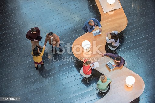 istock Business people sitting at curved wooden desk, high angle view 493796712