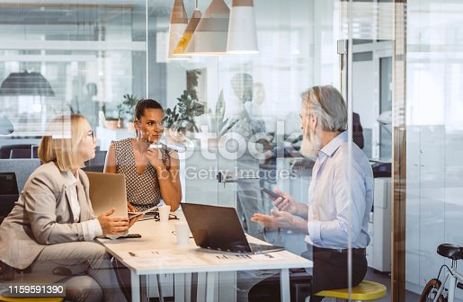 Business People Sitting at Desk, Discussing