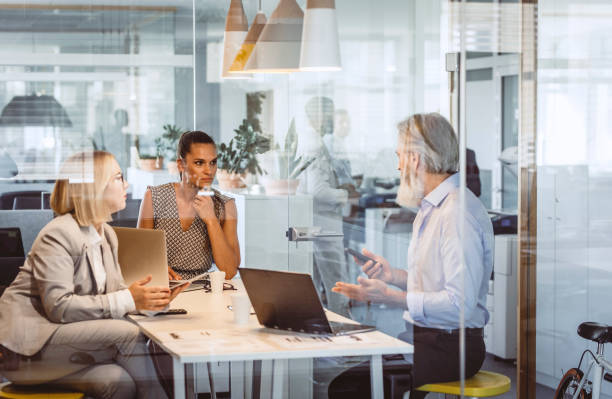 business people sitting at desk, discussing - definite stock pictures, royalty-free photos & images