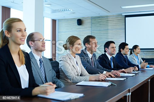 Business people sitting in a row at conference table and listening to presentation