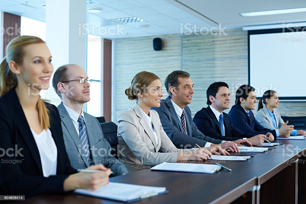 Business people sitting in a row at conference table stock photo