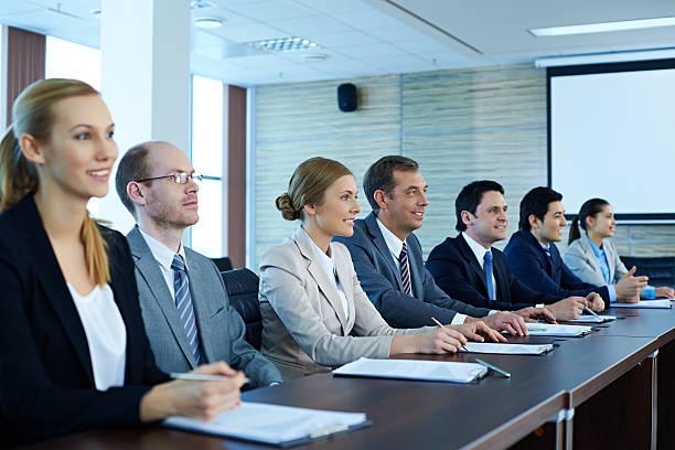 Uomini d'affari seduto in una riga al Tavolo da conferenza - foto stock