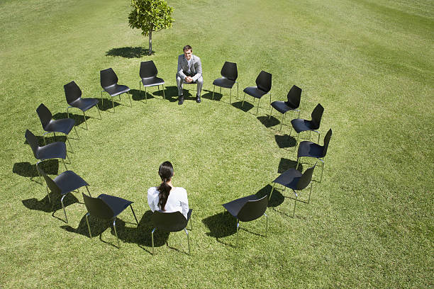 Business people sitting in circle of office chairs in field  samenwerking stock pictures, royalty-free photos & images