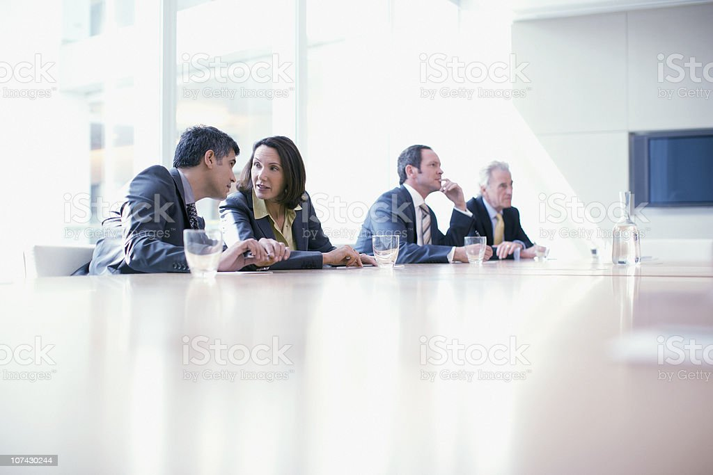 Business people sitting in conference room talking stock photo