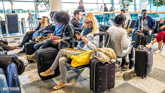 Business people sitting on chair at airport and using mobile phone.