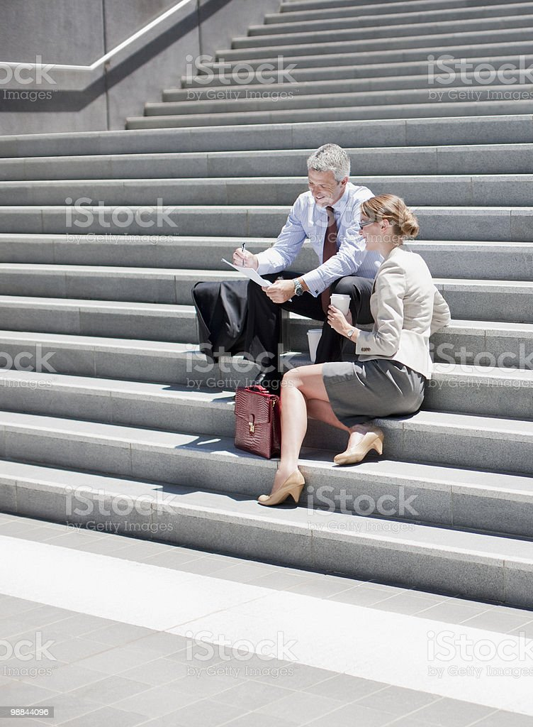 Business people sitting on steps outdoors royalty-free stock photo