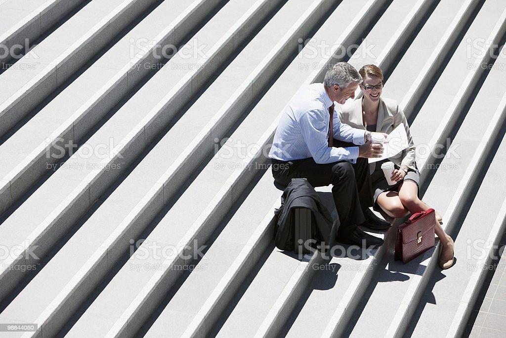 Pessoas de negócios sentado nas escadas a conversar ao ar livre foto de stock royalty-free